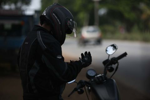 Man donning motorcycle gloves next to his motorcycle